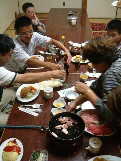 店員さんがすき焼きの肉や野菜を鍋に入れてくれる