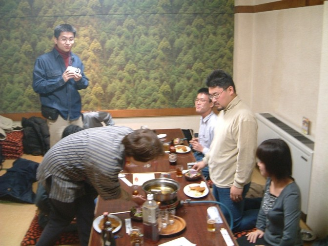 料理を撮影しようと身構える人多数の謎の部屋